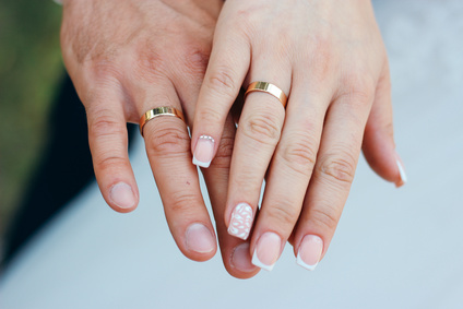hands of husband and wife with wedding rings.